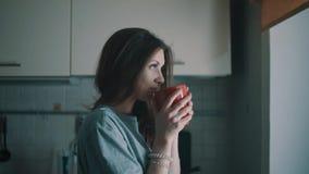 Het jonge glimlachende meisje kijkt in venster en drinkt koffie in keuken bij ochtend stock footage