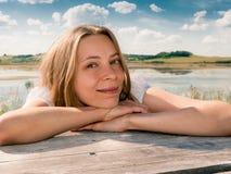 Het jonge glimlachende meisje leunt haar handen op houten lijst, en bekijkt camera op het landschapsachtergrond van het de zomerl Stock Afbeeldingen