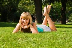 Het jonge glimlachende meisje ligt op gras royalty-vrije stock afbeelding