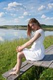 Het jonge glimlachende meisje in witte kleding is op houten lijst, en bekijkt camera op de achtergrond van het rivierlandschap in Royalty-vrije Stock Foto's