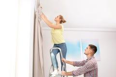 Het jonge gordijn van het paar hangende venster binnen stock foto