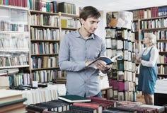 Het jonge het glimlachen boek van de mensenlezing terwijl Royalty-vrije Stock Foto