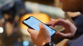 Het jonge hipsterkerel texting met zijn mobiele telefoon bij de bar voorraad Een jonge mens met een telefoon in van hem dient een stock foto's