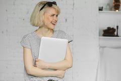 Het jonge hipstermeisje die met zonnebril en houdt laptop bij daglicht glimlachen royalty-vrije stock afbeelding