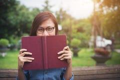 Het jonge hipstermeisje glimlachen en behandeld gezicht door haar rood boek whil royalty-vrije stock foto