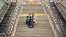 Het jonge houdende van paar neemt selfie zitting op de stappen van de universiteit stock footage