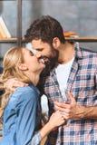 Het jonge houdende van paar omhelst en kussend Stock Afbeeldingen