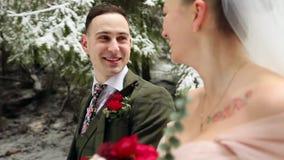 Het jonge huwelijkspaar die, het glimlachen en het spreken holding dient sneeuwbos tijdens sneeuwval in lopen Het huwelijk van de stock videobeelden