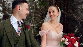Het jonge huwelijkspaar die, het glimlachen en het spreken holding dient sneeuwbos tijdens sneeuwval in lopen Het huwelijk van de stock footage