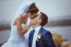 Het jonge huwelijkspaar kussen Stock Afbeeldingen