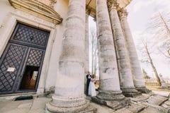 Het jonge huwelijkspaar stellen dichtbij antieke de bouwkolommen met leafless parkbomen bij achtergrond stock fotografie