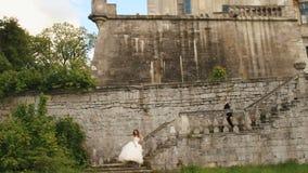 Het jonge huwelijkspaar stellen op oude steentreden Geruïneerde antieke kasteelvestingwerken als achtergrond stock videobeelden