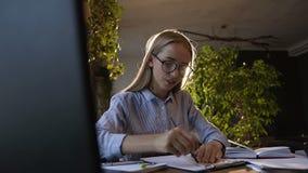 Het jonge ingenieursmeisje werkt in een modern bureau met rode bakstenen muur, concentreert en trekt blauwdrukken Jonge mooi stock video