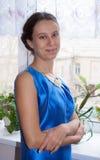 Het jonge jaren '20meisje in blauwe kleding bevindt zich dichtbij venster en het kijken Stock Foto