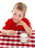 Het jonge jong geitje spelen met stuk speelgoed koe dichtbij glas melk stock afbeelding