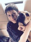 Het jonge jongen het glimlachen berijden in auto met zijn puppyhond stock afbeeldingen