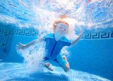Het jonge jongen onderwater spelen Stock Foto