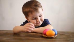 Het jonge jongen spelen met paaseieren thuis stock video