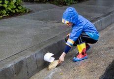 Het jonge jongen spelen met stuk speelgoed boot in regen 1 Royalty-vrije Stock Afbeeldingen