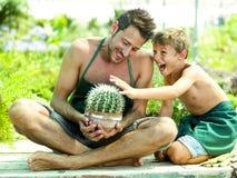 Het jonge jongen spelen met zijn vader in een serre royalty-vrije stock afbeeldingen