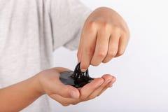 Het jonge jongen spelen met zwart slijm in zijn hand royalty-vrije stock fotografie