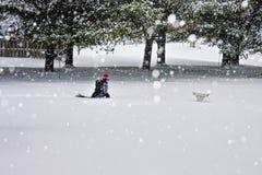 Het jonge jongen spelen in het midden van Sneeuwstorm stock foto