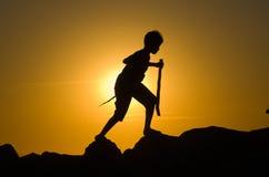 Het jonge jongen spelen op rotsen Stock Fotografie