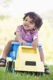 Het jonge jongen spelen op stuk speelgoed stortplaatsvrachtwagen in openlucht Royalty-vrije Stock Afbeeldingen