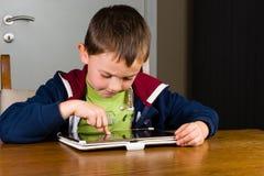 Het jonge jongen spelen op tabletcomputer royalty-vrije stock fotografie
