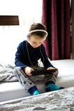 Het jonge jongen spelen op zijn mobiele telefoon in bed stock foto's