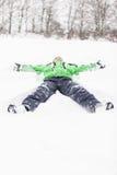 Het jonge jongen uit uitgerekt liggen in de sneeuw Royalty-vrije Stock Afbeeldingen