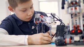Het jonge jongensingenieur spelen met robot Close-up stock video