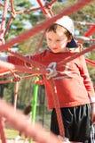 Het jonge jongenskind spelen bij het openluchtspeelplaats netto beklimmen stock afbeeldingen