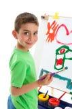 Het jonge jongenskunstenaar schilderen bij schildersezel royalty-vrije stock foto