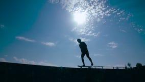 Het jonge jongenssilhouet schaatst op de rand van de omheining stock videobeelden