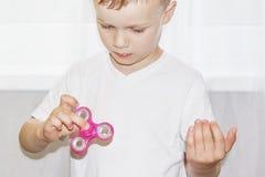 Het jonge jongensspel met friemelt het verlichtende stuk speelgoed van de spinnerspanning Populair stuk speelgoed Royalty-vrije Stock Fotografie