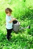 Het jonge jongenswater bloeit en groen gras met behulp van oude, grote en zware het water geven pot Jong geitjehulp met tuin van  royalty-vrije stock fotografie