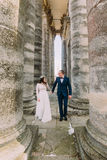 Het jonge jonggehuwdepaar stellen tussen rijen van antieke de bouwkolommen Stock Afbeelding