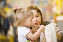 Het jonge Kaukasische mamma met haar dochter probeert op kleren Stock Afbeeldingen