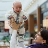 Het jonge Kaukasische mamma speelt met haar leuke heel zuigelingszoon, throing hem omhoog en vangt opnieuw bij openbare ruimte stock foto