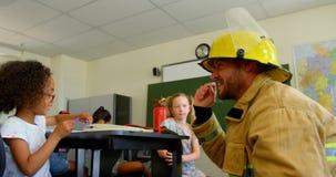 Het jonge Kaukasische mannelijke schoolmeisje van het brandbestrijdersonderwijs over brandveiligheid in klaslokaal 4k stock footage