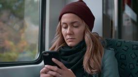 Het jonge Kaukasische meisje in een rode GLB-ritten op een metro of tramtreinauto, gebruikt de telefoon, drukt een bericht Langza stock video