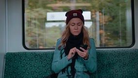 Het jonge Kaukasische meisje met blauwe ogenritten in een metro of tramtreinauto, gebruikt de telefoon, drukt een bericht en kijk stock video