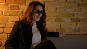 Het jonge Kaukasische meisje met golvend haar zet op 3D glazen en doet leunen op bank in positief vermaak op comfortabel huis stock footage
