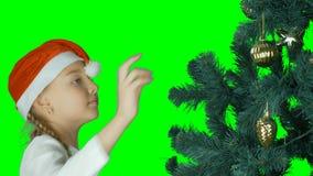 Het jonge Kaukasische meisje verfraait Kerstmisboom met gouden bal Groene Spar Meisje die gouden gebied op sparren hangen jong stock video