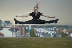 Het jonge Kaukasische meisje voert streng uit springend over achtergrondcityscape royalty-vrije stock foto