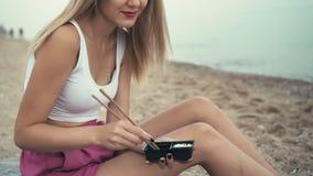 Het jonge Kaukasische onherkenbare meisje beweegt wasabi in sojasaus alvorens sushi op de oceaan overzeese kust te eten Zit op za stock videobeelden