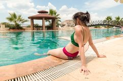 Het jonge Kaukasische vrouw ontspannen dichtbij zwembad in een toevlucht stock afbeelding