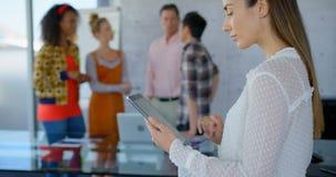 Het jonge Kaukasische vrouwelijke uitvoerende werken aan digitale tablet in modern bureau 4k stock videobeelden
