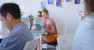 Het jonge Kaukasische vrouwelijke uitvoerende werken bij bureau in modern bureau 4k stock videobeelden